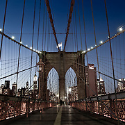 People on the Brooklyn Bridge by night.