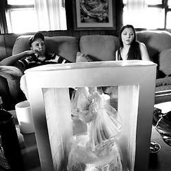 "Engaged couple, Jessica White (right, age 17), and Casey Dalton (left, age 17), watch television at Casey's parents house as a wedding cake topper from Wal-Mart sits on the coffee table in front of them. Jessica, who is a senior at William Fleming, and Casey, who recently received his GED, have been dating since August, and currently live together at Casey's parents house. Jessica and Casey attended William Fleming's ""A Night in Paris"" prom hours after getting married. Monday, Jessica will be back at William Fleming to finish here senior year, while Casey will go back to his job as a diesel mechanic."