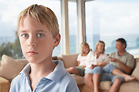 Boy Standing in Room with Family in Background