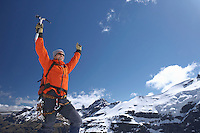 Mountain climber with arms raised on top of peak