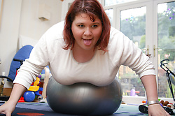 Woman at home exercising on a Swiss ball,