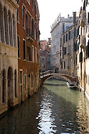 A woman crossing a bridge over a canal in Venice, Italy