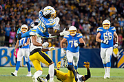 Los Angeles Chargers running back Melvin Gordon (25) jumps over Pittsburgh Steelers defenders free safety Minkah Fitzpatrick (39) strong safety Terrell Edmunds (34) during an NFL football game, Sunday, Oct. 13, 2019, in Carson, Calif. (Ed Ruvalcaba/Image of Sport)