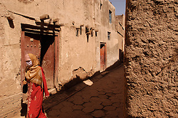 Veiled uyghur woman walking past mud walled houses in old city of Kashgar in Xinjiang Province of China 2003