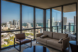The living room of a two-bedroom, furnished corner unit at Canvas. All the units feature floor to ceiling windows.