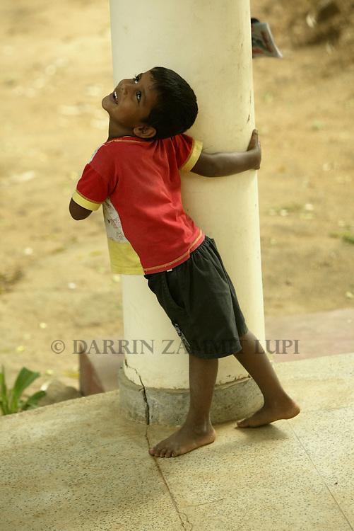 A young boy plays outside a government building in Hambantota, Sri Lanka, on January 16. 2005..Photo by Darrin Zammit Lupi