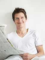 Young man reading newspaper in bed looking to side and smiling