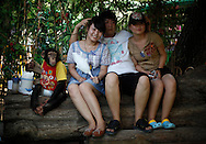A man poses for a picture with two women and a chimpanzee at the Zoo in Beijing, China, Thursday, Aug. 13, 2009.