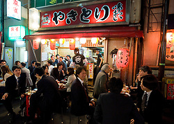 Night view of typical busy Japanese restaurant or Izakaya on street in central Tokyo