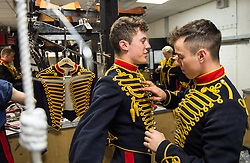 © London News Pictures. 14/07/2015.  Gunner Brandon Dunn helps his colleague Gunner Myles Robertson into his kit.<br />  . More usually associated with the ceremonial gun salutes and musical rides with their 13lb guns, they took on the role of both mounted and dismounted guard at the entrance of Horse Guards. This year, for the first time, they are using Knightsbridge Barracks, the home of the Household Cavalry Mounted Regiment, for the period of their duty, as opposed to Wellington Barracks, which they have used in previous years.  Photo credit: Sergeant Rupert Frere/LNP