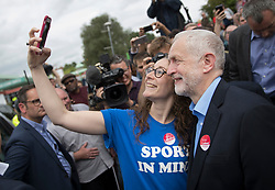 © Licensed to London News Pictures. 31/05/2017. Reading, UK. Leader of the Labour Party JEREMY CORBYN stops for a selfie photograph with a supporter during a rally at Rivermead Leisure Centre in Reading, Berkshire, ahead of a general election on June 8. Mr Corbyn has announced that he will join an seven way election debate tonight in Cambridge. Prime Minister Theresa May has said she will not attend. Photo credit: Peter Macdiarmid/LNP