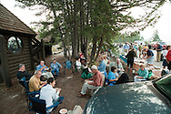 PRICE CHAMBERS / NEWS&amp;GUIDE<br /> People gather outside the chapel for a celebratory cookout following Mass. Surrounded by trees, the building is just a short distance from the banks of Jackson Lake.