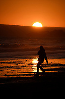 Person walking through a sunset at the beach