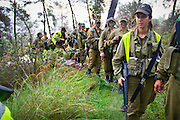Israeli women in the army participate in a pre-dawn march wearing full army uniforms and equipment. Central Israel. Photography by Debbie Zimelman