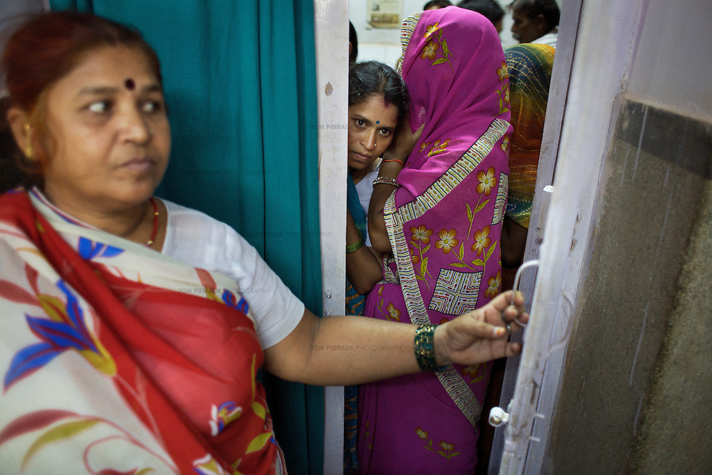 Women wait in line for a consultation with gynecologist Dr. Veena Kumra at the Shivpuri District hospital. Like many of India's public hospitals, this facility is over subscribed and under resourced. ..Shivpuri district in Madhya Pradesh suffers from poor health outcomes. Of particular concern is the high rate of maternal mortality. One of the Indian government's aims, with partners Unicef, is to encourage the population to adopt practices to improve sanitation and health practices. In an area made up of traditionally disadvantage groups and suffering low literacy rates, this can be a challenge. ..A survey found that radio was the most readily accessible media by the Shivpuri community with more than half saying they tuned in several times a day. ..Dharkan 107.8 FM will go on air in July. The station that will broadcast to 75 villages in a 15-kilometer radius reaching 170,000 people...Rather than preaching educational messages, the station, which is already producing pilot programs, uses humor and folk artists performing in the local language to entertain and inform their audiences. There is a major impact, especially on women, who are contributing their voices to such wide-ranging issues as caste discrimination, female feticide and women,A?o?s empowerment. ..Photo: Tom Pietrasik.Shivpuri, Madhya Pradeh. India.June 2009