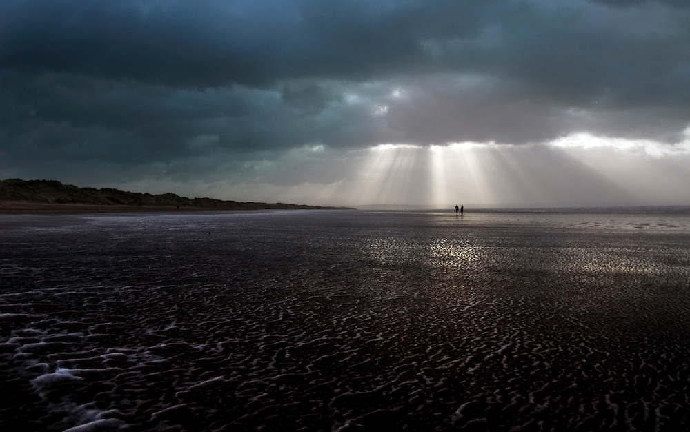 Surfers caught in rays of sunlight as they walk towards shore. Saunton Sands, North Devon, England.