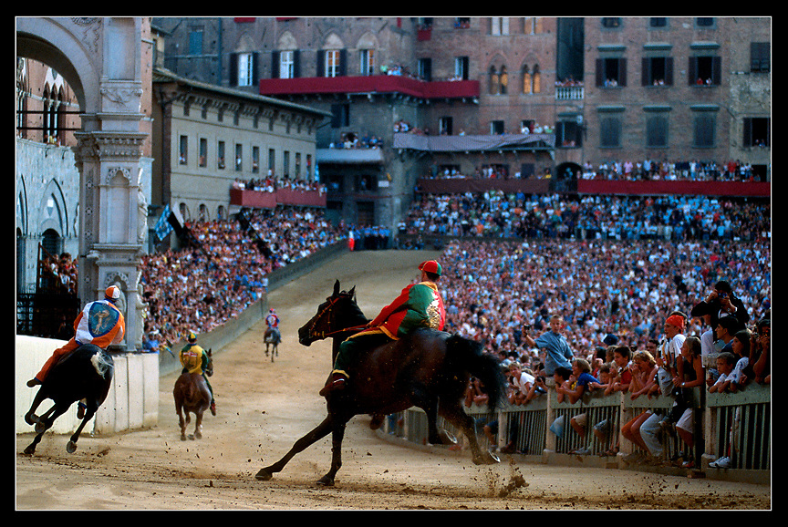 The Piazza Del Campo is alive with cheers and emotion from the Sienese and tourists alike as the jockeys ride their horses bareback around the bend at San Martino. The entire event culminates with one race that circles the piazza three times.