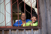A grandmother and grandson looking out of the window smiling.