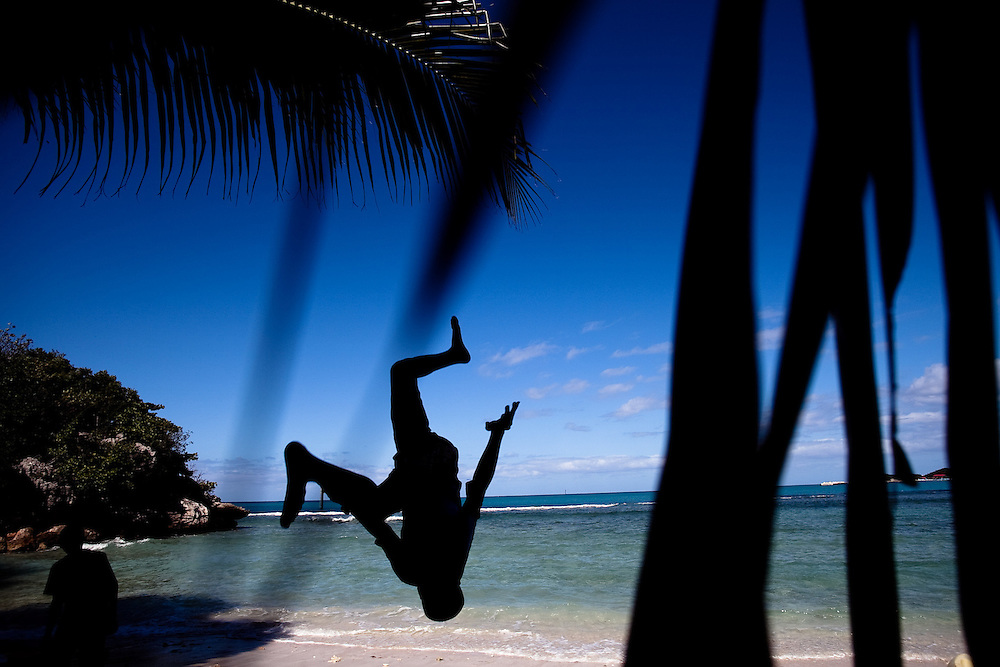 A boy does a flip on the beach in the village of Labadie.