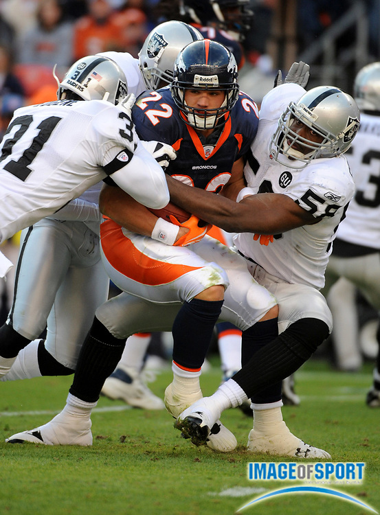 Nov 23, 2008; Denver, CO, USA; Denver Broncos fullback Peyton Hillis (22) is tackled by Oakland Raiders safety Hiram Eugene (31), safety Michael Huff (24) and defensive end Kalimba Edwards (58) in the first half at Invesco Field. The Raiders defeated the Broncos 31-10.