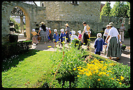 Schoolkids & women dressed as peasants visit gardens at Ecomusee folk museum; Ungersheim, Alsace. France