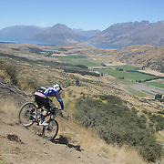 JD Devlin from Christchurch in action during the New Zealand South Island Downhill Cup Mountain Bike series held on The Remarkables face with a stunning backdrop of the Wakatipu Basin. 150 riders took part in the two day event. Queenstown, Otago, New Zealand. 9th January 2012. Photo Tim Clayton