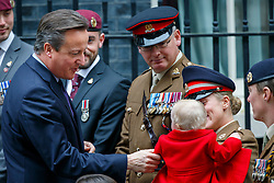 © Licensed to London News Pictures. 22/10/2015. London, UK. Prime Minister David Cameron meets Jodie Older and her baby Isebella Older before buying a Royal British Legion poppy in Downing Street, London on Thursday, 22 October 2015. Photo credit: Tolga Akmen/LNP