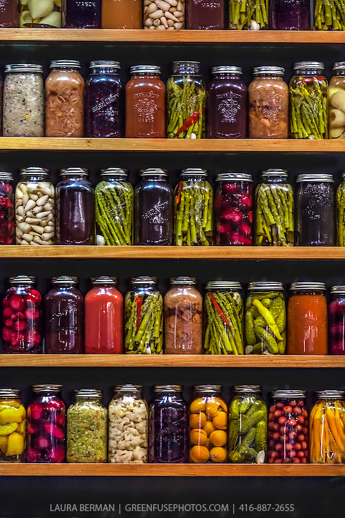 Shelves of a variety of pickled vegetables and preserved fruits in clear glass mason jars by Canadian chef Jamie Kennedy.