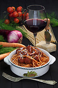 Bowl with spaghetti and meatballs on table with glass of red wine and fresh vegetables.