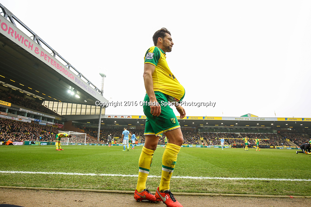 12 March 2016 - Barclays Premier League - Norwich City v Manchester City - Russell Martin of Norwich City walks past with a football up his shirt - Photo: Marc Atkins / Offside.