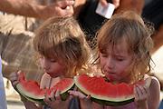 Israel, Tel Aviv The beach Twins girls eating watermellon