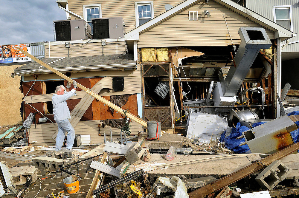 A man helps to remove debris and board up the storm-ravaged Bayside Grill in Keyport four days after Hurricane Sandy made it's way through the area on November 2. Hurricane Sandy forced the shutdown of mass transit, schools and financial markets, sending coastal residents fleeing for higher ground, and threatened a dangerous mix of high winds and soaking rain.