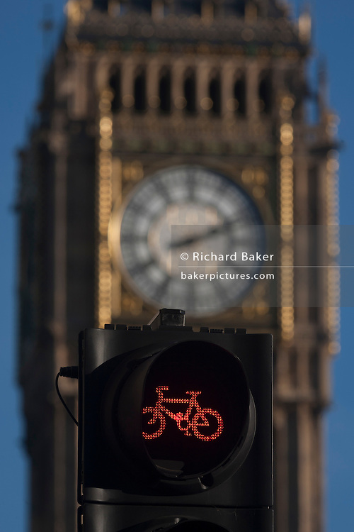A red cycling light in the foreground and the clockface containing the Big Ben bell in the Elizabeth Tower of the British parliament, on 17th January 2017, in London England. The Elizabeth Tower (previously called the Clock Tower) named in tribute to Queen Elizabeth II in her Diamond Jubilee year – was raised as a part of Charles Barry's design for a new palace, after the old Palace of Westminster was largely destroyed by fire on the night of 16 October 1834. The new Parliament was built in a Neo-gothic style. Although Barry was the chief architect of the Palace, he turned to Augustus Pugin for the design of the clock tower. It celebrated its 150th anniversary on 31 May 2009. The tower was completed in 1858 and has become one of the most prominent symbols of both London and England.