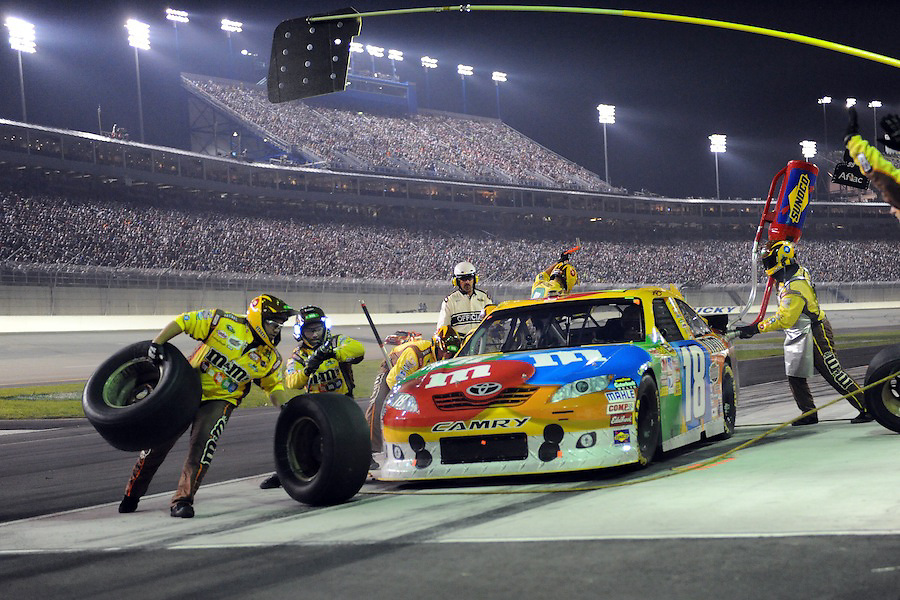 The pit crew for Kyle Busch's M&M's Toyota finish the left side of the car during a four tire stop late in the inaugural Quaker State 400 at the Kentucky Speedway in Sparta, Kentucky. Kyle Busch won the race after starting on the pole.