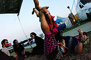 A woman lifts a child with her legs while three people look on, Boomtown, Matterley Estate, Alresford Road,  Winchester, Hampshire, UK, August, 2010