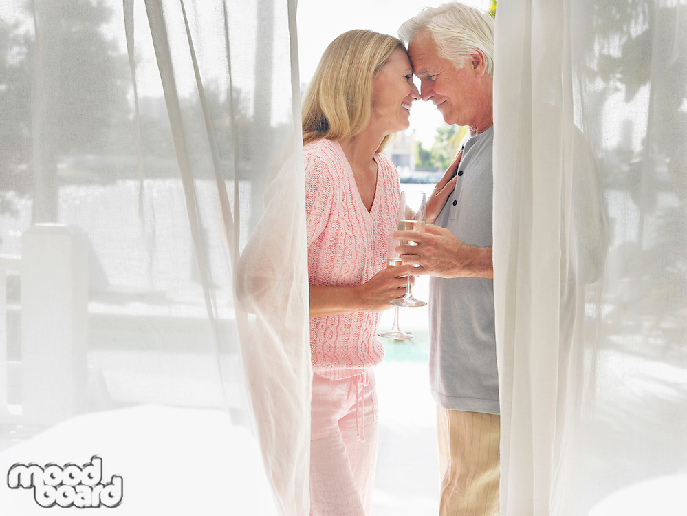 Couple standing on verandah face to face side view