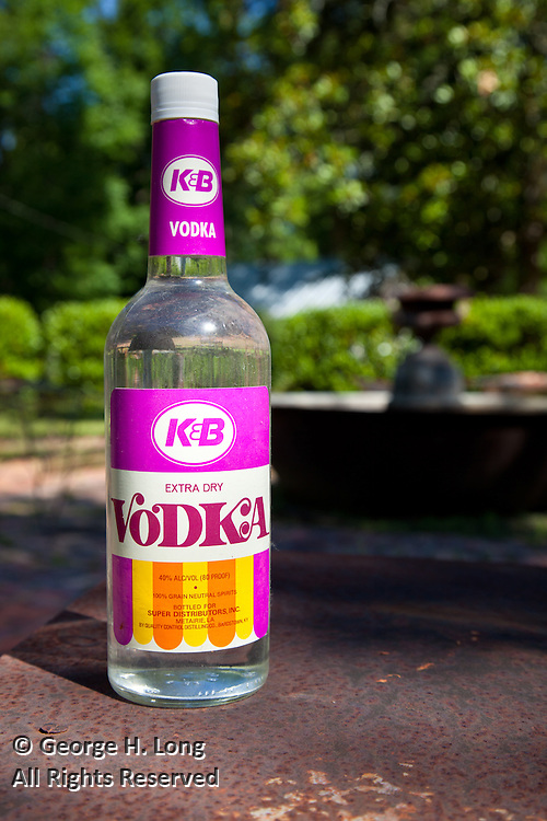 """a dusty, old bottle of K&B brand vodka found at the Blitch family home, """"Ahmeek"""" in Abita Springs; Katz & Besthoff drug store's colorful bottle and logo"""
