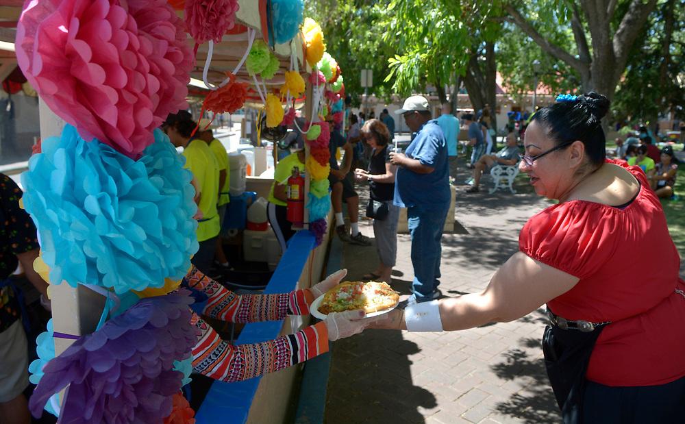 gbs060417g/ASEC -- Yolanda Ballejos of Albuquerque, buys an indian taco during the San Felipe de Neri Fiesta on Sunday, June 4, 2017. (Greg Sorber/Albuquerque Journal)