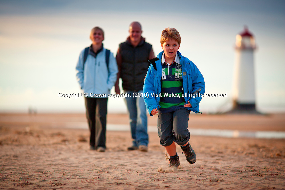 Family (parents and young son walking <br /> Wales Coast Path<br /> Talacre Lighthouse<br /> Near Point of Ayr<br /> Flintshire<br /> North<br /> Activities and Sports