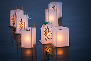 A group of paper lanterns, some with origami cranes affixed to the top, float in the waters of Green Lake during the annual From Hiroshima to Hope event, which observes the anniversary of the Hiroshima and Nagasaki atomic bombings. <br /> <br /> Lindsey Wasson / The Seattle Times