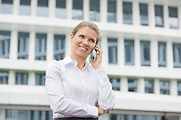 Smiling businesswoman using cell phone outside office