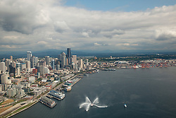 North America, United States, Washington, Seattle aerial view of downtown skycrapers, fireboat spraying fountain in Puget Sound, stadiums and Port of Seattle