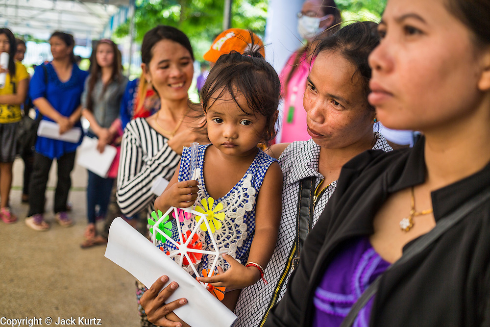 "17 JULY 2014 - BANGKOK, THAILAND: Undocumented Cambodian women and their children wait for their chance to apply for temporary Thai ID cards and work permits at the temporary ""one stop service center"" in the Bangkok Youth Center in central Bangkok. Thai immigration officials have opened several temporary ""one stop service centers"" in Bangkok to register undocumented immigrants and issue them temporary ID cards and work permits. The temporary centers will be open until August 14.    PHOTO BY JACK KURTZ"
