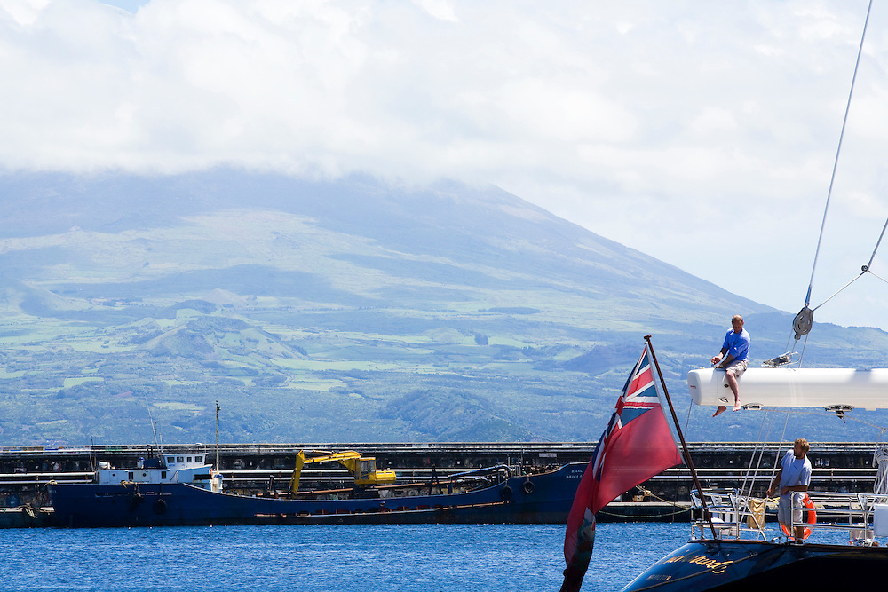 Crew members work against a backdrop of the neighboring island of Pico.The Azores are a group of islands under Portuguese sovereignty. They Mark the most westerly point of the E.U. and earn most of their income from agriculture and tourism.