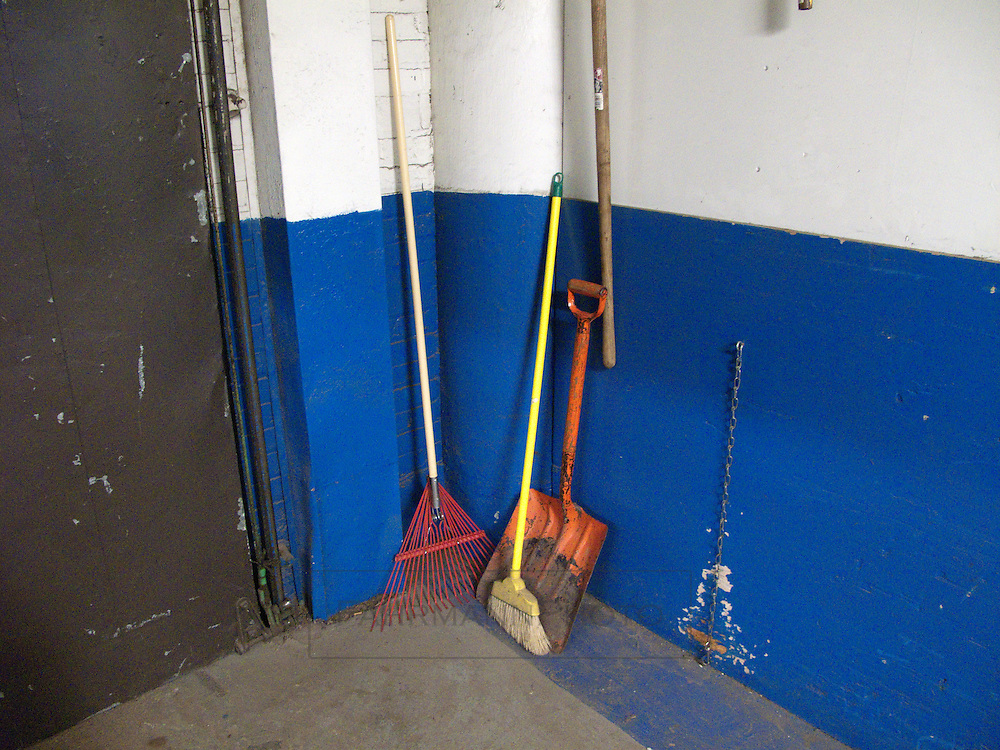 Colorful tools sit against the blue wall in the corner of a warehouse near a door