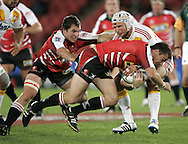 JOHANNESBURG, SOUTH AFRICA - 23 April 2011: Cobus Grobbelaar helps Doppie Le Grange drive with ball while makes a tackle during the Super Rugby Match between the MTN Lions and the Chiefs held at Coca Cola Park Stadium, Johannesburg, South Africa. Photo by Dominic Barnardt
