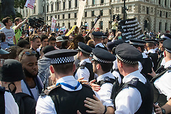 London, June 21st 2017. Protesters march through London from Sheherd's Bush Green in what the organisers call 'A Day Of Rage' in the wake of the Grenfell Tower fire disaster. The march is organised by the Movement for Justice By Any Means Necessary and coincides with the Queen's Speech at Parliament, the destination. PICTURED: Police push protesters off the road outside Parliament.