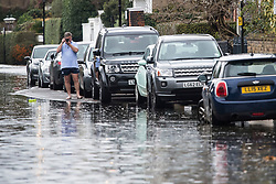 © Licensed to London News Pictures. 01/01/2018. London, UK. A local resident takes a picture of flood water covering the roads along the embankment at Chiswick in West London where the River Thames has broken it's banks. Photo credit: Ben Cawthra/LNP