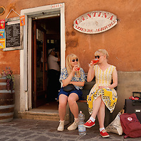"VENICE, ITALY - JUNE 17:  Two tourists enjoy a Spritz (a powerful mixture of white wine, Campari and soda water) in front of a traditiona bacaro on June 17, 2011 in Venice, Italy. The bacari are the local down to earth version of wine bars, they serve  ""cicheti"" a sort of Tapas, traditionally washed down with a glass of wine, and Venetians stop to snack and socialize before and after meals..."