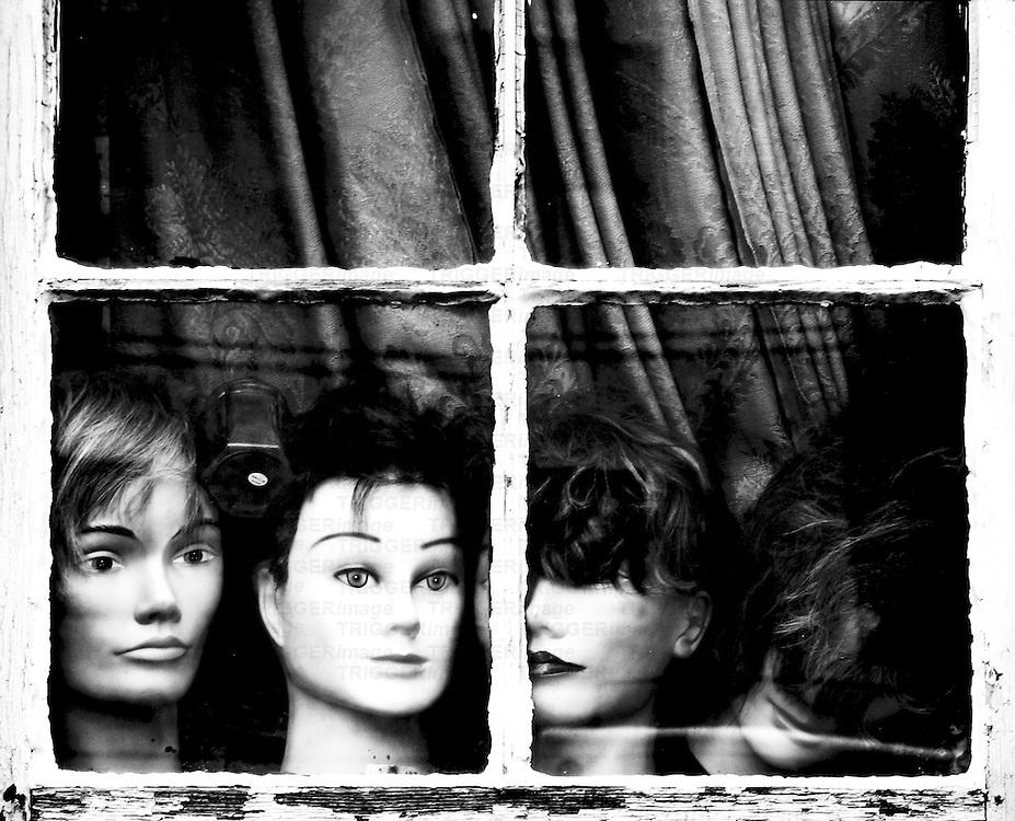 Dummies heads in an old window